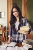 Kvinnastudent med glasögon som rymmer pappers- böcker arkivbilder