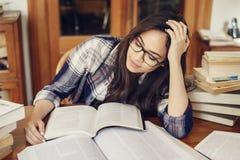 Kvinnastudent som läser en mycket trött bok royaltyfri foto