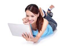 Kvinnastudent som ligger och använder den digitala minnestavlan Fotografering för Bildbyråer