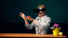 Kvinnastudent som skriver med vr Apparat f?r VR-h?rlurar med mikrofonexponeringsglas Svart tavlabakgrund Skola och utbildningsbeg stock video