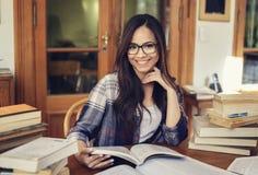 Kvinnastudent som studerar med många böcker royaltyfri fotografi