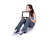 Kvinnastudenten sitter och genom att använda den digitala minnestavlan Royaltyfri Fotografi