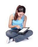 Kvinnastudenten sitter och genom att använda den digitala minnestavlan Royaltyfri Foto