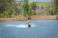 Kvinnastudie som wakeboarding på en blå sjö Fotografering för Bildbyråer