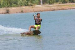 Kvinnastudie som wakeboarding på en blå sjö Arkivbilder