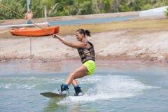 Kvinnastudie som wakeboarding på en blå sjö Royaltyfria Foton