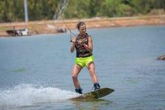 Kvinnastudie som wakeboarding på en blå sjö Royaltyfri Fotografi