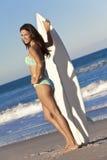 Kvinnasurfare i bikini med surfingbrädan på stranden Royaltyfri Foto