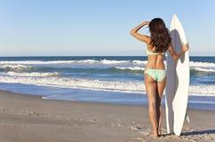 Kvinnasurfare i bikini med surfingbrädan på stranden Arkivfoto