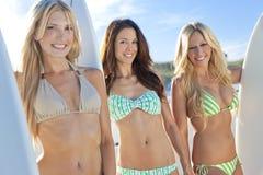 Kvinnasurfarear i bikinier med surfingbrädor på Beac royaltyfri fotografi