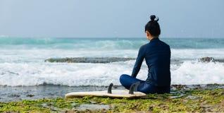 Kvinnasurfaren sitter på reven arkivbilder
