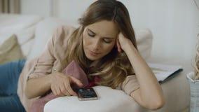 Kvinnasvarstelefon på soffan hemma Talande mobil för kvinnlig person på soffan arkivfilmer