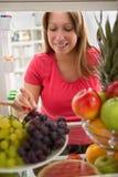 Kvinnatagandekorn av druvor och att smaka det Arkivfoto