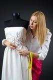 Kvinnatailor som fungerar på klänningen Arkivbild
