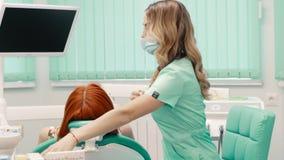 Kvinnatandläkaren ger fem av hennes patient arkivfilmer