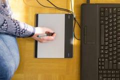 Kvinnateckning på en grafisk minnestavla med pennan och bärbara datorn Royaltyfri Bild