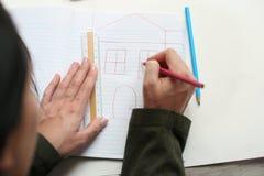 Kvinnateckningshus på papper med färgblyertspennor och en linjal arkivfoto