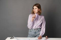 Kvinnateckningsintrig En på en grå bakgrund Arkivfoto