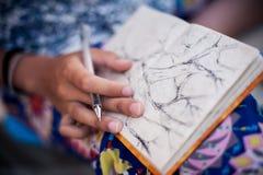 Kvinnateckningsträd i hennes anteckningsbok Arkivfoto