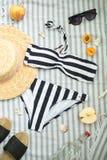 Kvinnatillbehör på stranden, baddräkten, hatten och exponeringsglasen arkivbilder