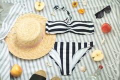 Kvinnatillbehör på stranden, baddräkten, hatten och exponeringsglasen royaltyfri bild