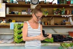 Kvinnaträdgårdsmästaren som wokar i en trädgård, shoppar Arkivfoto