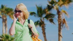 Kvinnaturist i solglasögon som talar på telefonen på bakgrunden av himmel och palmträd stock video