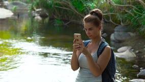 Kvinnaturist med ryggsäckdanandefotoet på mobiltelefonen, medan trekking i den unga kvinnan för djungelskog som använder smartpho arkivfilmer