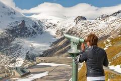 Kvinnaturist med teleskopet i Grossglockner, höga fjällängar, Österrike Arkivbilder