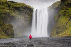 Kvinnaturist på den Skogafoss vattenfallet Arkivbilder