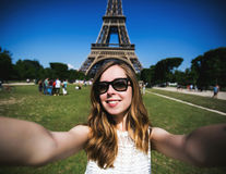 Kvinnaturist på Eiffeltorn som ler och gör Royaltyfria Bilder