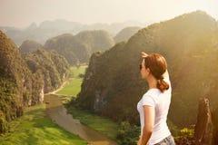 Kvinnaturist som ser långväga och tycker om dal- och kullesikt från överkant av ett berg arkivbilder
