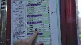 Kvinnaturist som ser schema- och ruttpassagerarebussar i station i modernasian stad för M Kvinnliga handflyttningar fingrar på lager videofilmer