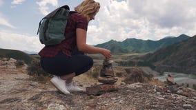 Kvinnaturisten gör en pyramid av stenar Handelsresande i bergen stock video