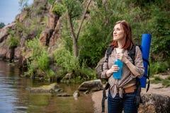 Kvinnaturisten med en ryggs?ck g?r i en vandring mot en bakgrund av h?rligt berglandskap l?ngs en bergflod arkivbild