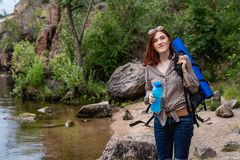 Kvinnaturisten med en ryggs?ck g?r i en vandring mot en bakgrund av h?rligt berglandskap l?ngs en bergflod arkivfoto