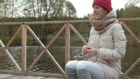 Kvinnaturisten sitter på bron nära floden, matar hunden utomhus- aktiviteter och en sund livsstil i sommaren arkivfilmer