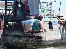 Kvinnatvagning själv på ett fartyg Cai Rang som svävar marknaden, Can Tho Arkivfoton