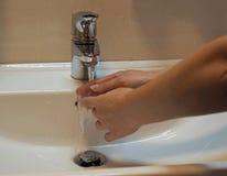 Kvinnatvagninghänder i badrumvask Arkivfoto