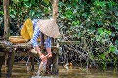 Kvinnatvagningkläder i Mekonget River Royaltyfri Bild