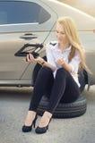 Kvinnauppehälle en stålar Bruten bil på en bakgrund Kvinnan sitter på ett hjul kvinnareparation en bil Naturlig bakgrund Bilaccid Fotografering för Bildbyråer