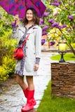 Kvinnauppklädd i en regnrock med ett paraply Fotografering för Bildbyråer