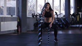 Kvinnautbildning i idrottshall med stridrep Kraftig attraktiv caucasian kvinna att göra stridgenomkörare med rep på idrottshallen stock video