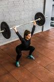 Kvinnautbildning squats med skivstånger uppe i luften Royaltyfri Bild
