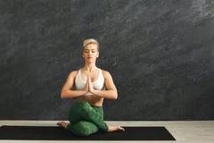 Kvinnautbildningsyoga i kohuvud poserar i idrottshall Royaltyfri Foto
