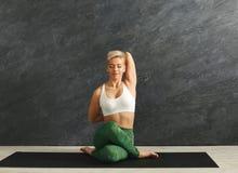 Kvinnautbildningsyoga i kohuvud poserar i idrottshall Royaltyfria Foton