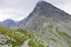 Kvinnavälkomnande till steniga slingor för berg Arkivbild