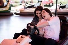 Kvinnavänner som kör radiobilen i nöjesfältet och att ha gyckel arkivfoto