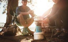 Kvinnavärmehänder på ugnen på campingplatsen royaltyfria foton