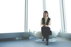 Kvinnavd:n med celltelefonen i händer sitter i modern kontorsinre mot skyskrapafönster arkivfoton